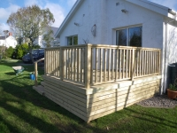 Decking off patio doors. This decking has the underneath boxed in with extra timber, and includes and extra wide set of steps and gate for easier access.