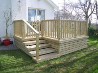 Decking off patio doors. This decking has the underneath boxed in with extra timber, and includes and extra wide set of steps and gate for easier access. The gate means that the dog can be kept in.