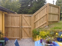 Featheredge Fence that is a complicated shape on different levels and bends away near the higher level. includes a door with a heavy duty suffolk latch