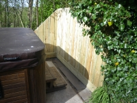 Fencing around a hot tub with different sized vertical timbers to create a new effect