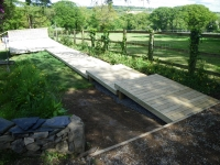 walkway made from smooth decking boards leading to a larger decked area